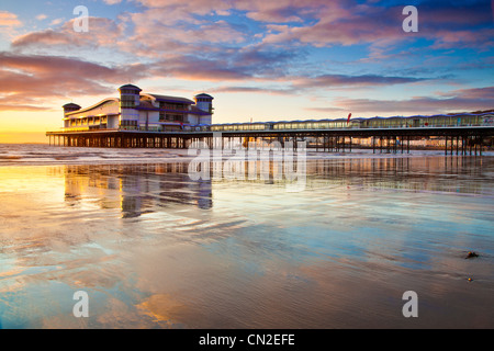 Sunset over the Grand Pier at Weston-Super-Mare, Somerset, England, UK reflected in the wet sand of the beach at - Stock Photo