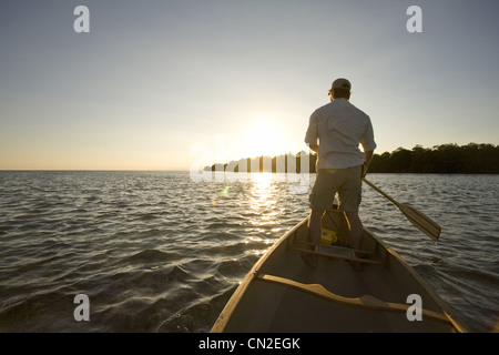 Man Standing and Paddling Boat at Sunset, Florida Keys, USA - Stock Photo