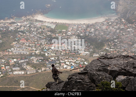 Abseiling from Table Mountain Cape Town, South Africa showing Camps Bay - Stock Photo