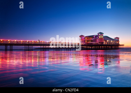 Twilight over the illuminated Grand Pier at Weston-Super-Mare, Somerset, England, UK reflected in wet sand at high - Stock Photo
