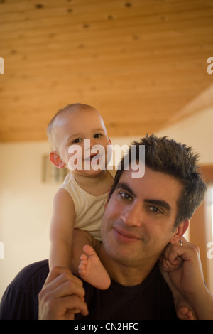 Father carrying baby boy on shoulders - Stock Photo