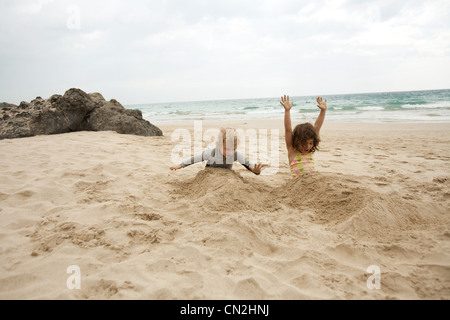 Boy and girl buried in sand on beach - Stock Photo