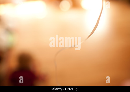 Blurred figure sitting on floor with balloon ribbon - Stock Photo