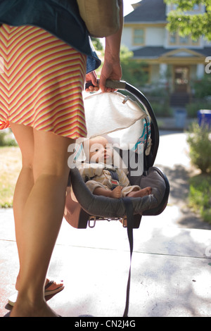 Mother carrying newborn baby boy in car seat - Stock Photo