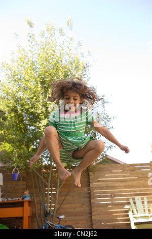 Young girl jumping on trampoline - Stock Photo