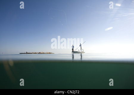 Over and Underwater View of Two Men Fly Fishing in Boat Near Shipwreck, Florida Keys, USA - Stock Photo