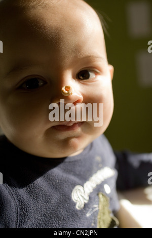 Baby boy with breakfast cereal on nose - Stock Photo