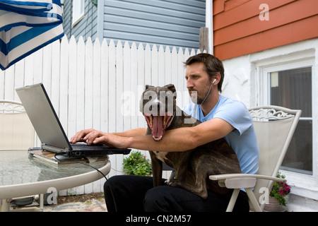 Man using laptop with dog sitting on lap - Stock Photo