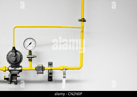Yellow industrial pipes and pressure guage - Stock Photo