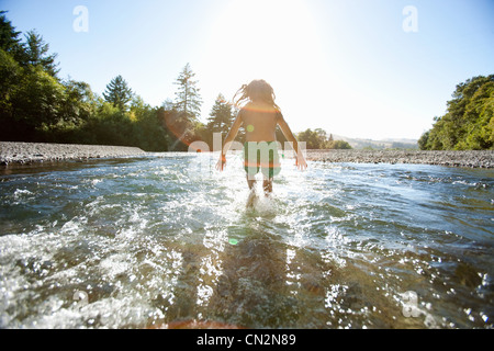 Girl jumping in river - Stock Photo