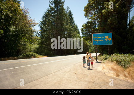 Family standing at roadside by sign saying welcome to California - Stock Photo