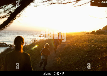 Family walking by coast at sunset - Stock Photo