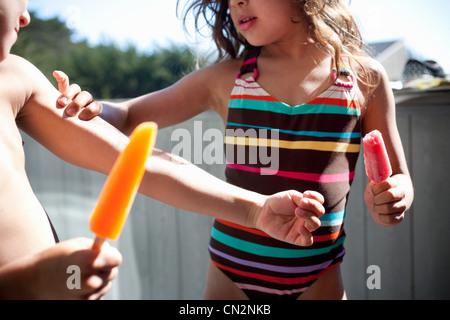 Children eating ice lollies - Stock Photo