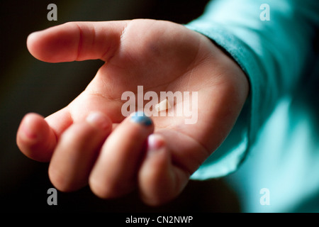 Girl holding tooth in palm of hand, close up - Stock Photo