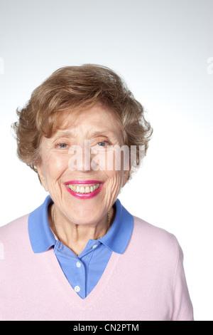 Senior woman looking at camera, studio shot - Stock Photo