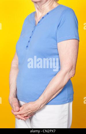 Senior woman with hands clasped, studio shot - Stock Photo