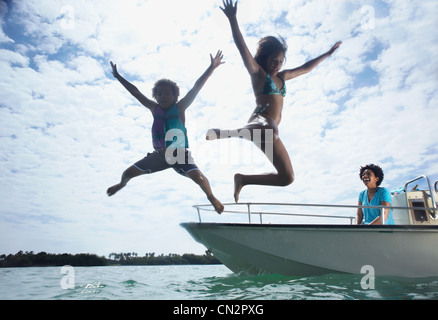 Mother on motorboat, two children jumping into water - Stock Photo