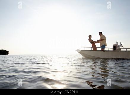 Senior couple holding hands on motorboat - Stock Photo