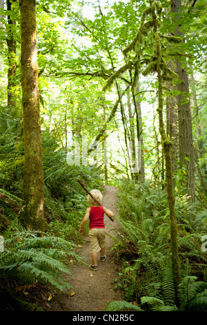 Young boy walking along forest path - Stock Photo