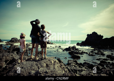 Mother, son, daughter, look out over southern ocean, Cape Palliser, New Zealand. - Stock Photo