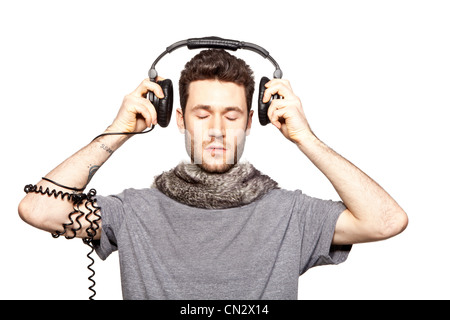 Young man putting on headphones - Stock Photo