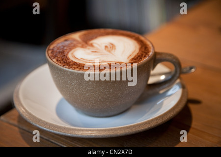 Cappuccino with heart shape in froth - Stock Photo