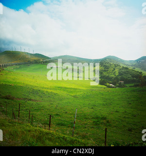 Wind turbines on hill in distance - Stock Photo