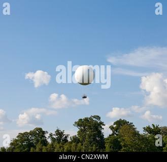 White hot air balloon above trees