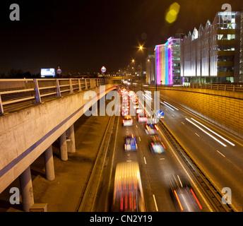 Traffic on road in urban scene at night, London, England - Stock Photo