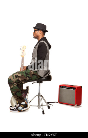 Man sitting on stool with electric guitar - Stock Photo