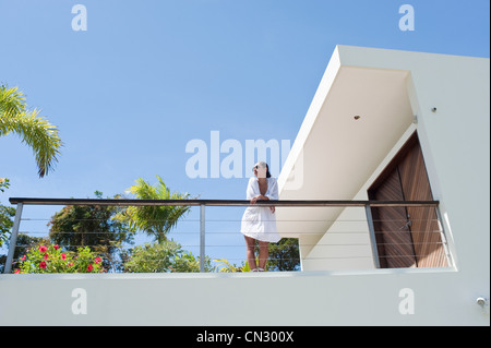 Young woman on apartment balcony in sunlight - Stock Photo