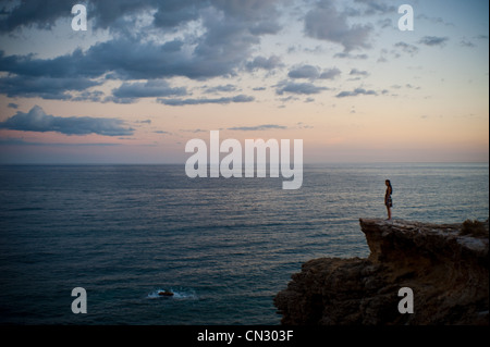Woman standing on cliff looking out to sea at sunset - Stock Photo
