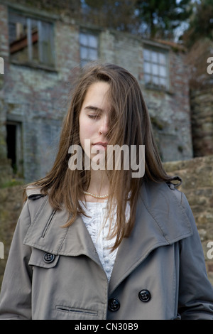 Teenage girl with eyes closed in front of derelict building - Stock Photo