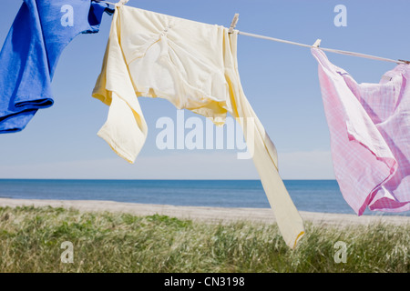 Laundry drying on clothes line by sea - Stock Photo