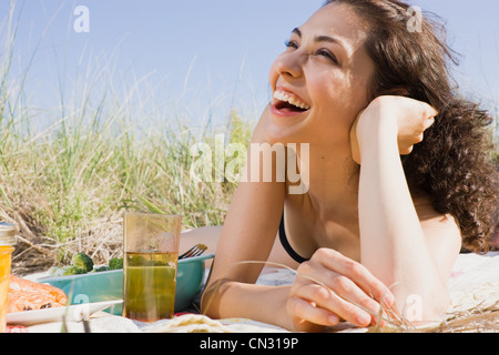 Woman laughing on picnic blanket - Stock Photo