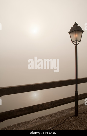 Lamp post by wooden fence - Stock Photo