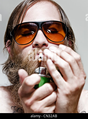 Portrait of young man lighting cigarette, close up - Stock Photo