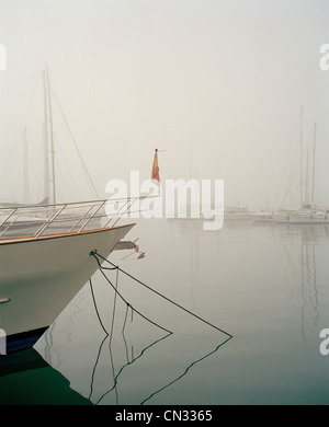 Boats in harbour in fog - Stock Photo