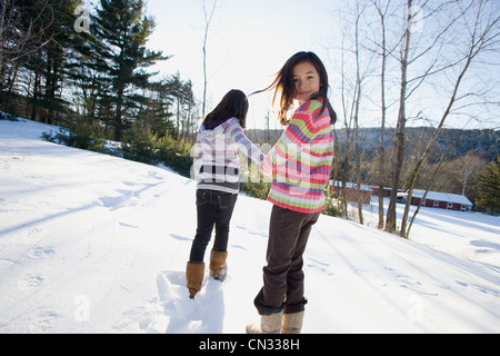 Two girls walking in the snow - Stock Photo