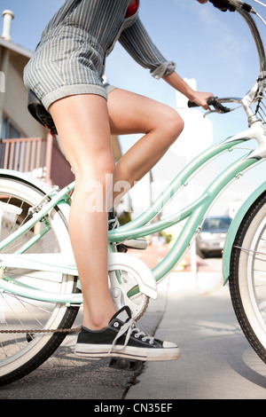 Young woman riding bicycle - Stock Photo