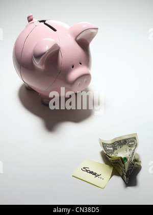 Broken piggy bank with one dollar bill and note saying sorry - Stock Photo