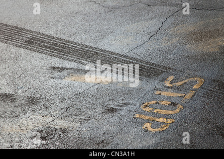 Tire tracks and stop sign - Stock Photo