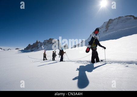 Four men carrying snowboards in snow - Stock Photo