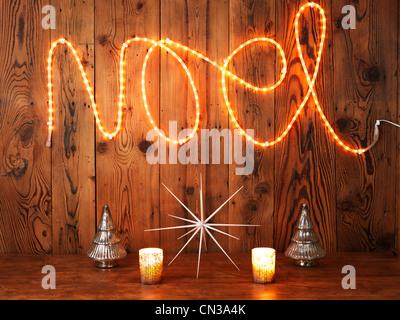Christmas lights spelling Noel against wood panelling - Stock Photo