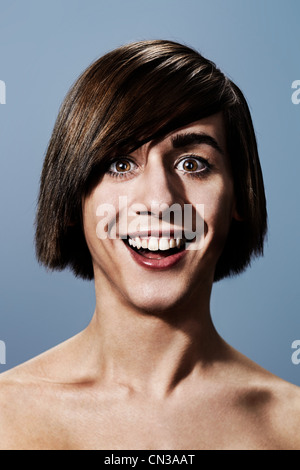 Smiling young man with bobbed hair - Stock Photo