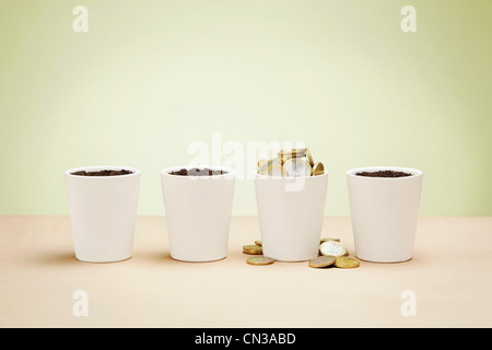 Four plant pots, one full of euro coins - Stock Photo