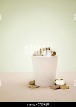 Plant pot full of euro coins - Stock Photo