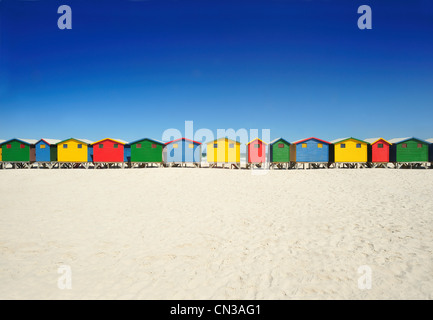 Brightly colored beach huts on beach - Stock Photo