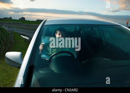 Businessman reading map in car - Stock Photo