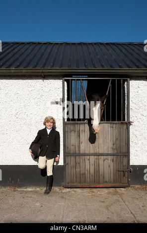 Boy standing by horse stables - Stock Photo